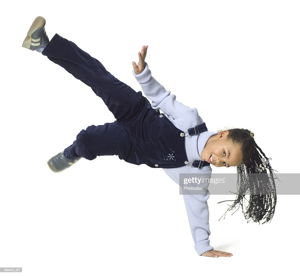 full body shot of a female child as she jumps up on her hand : Stockfoto