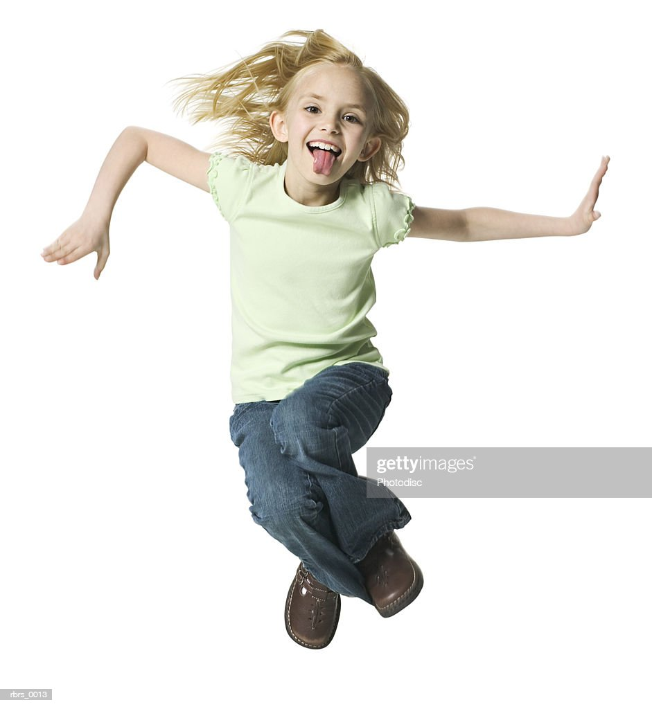full body shot of a female child as she jumps up playfully into the air : Foto de stock