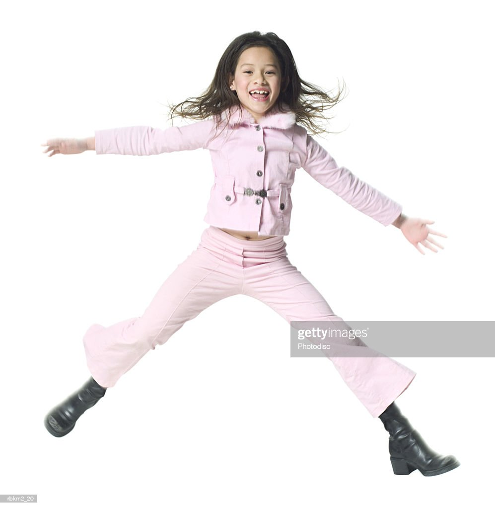 full body shot of a female child as she jumps up playfully through the air : Stockfoto