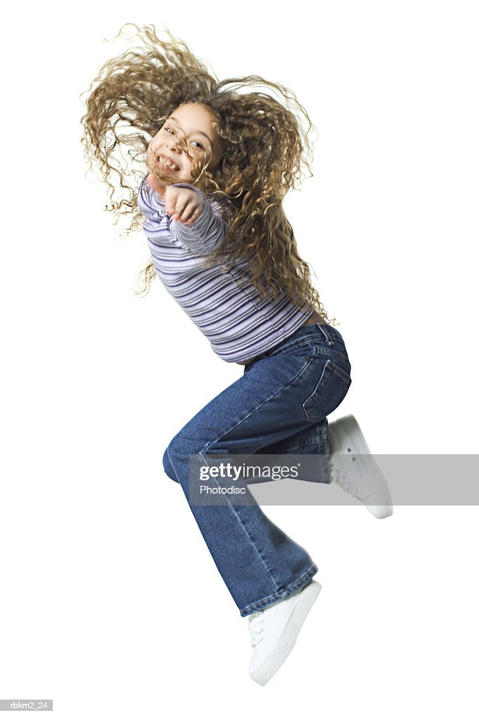 full body shot of a female child as she jumps up wildly through the air : Stockfoto