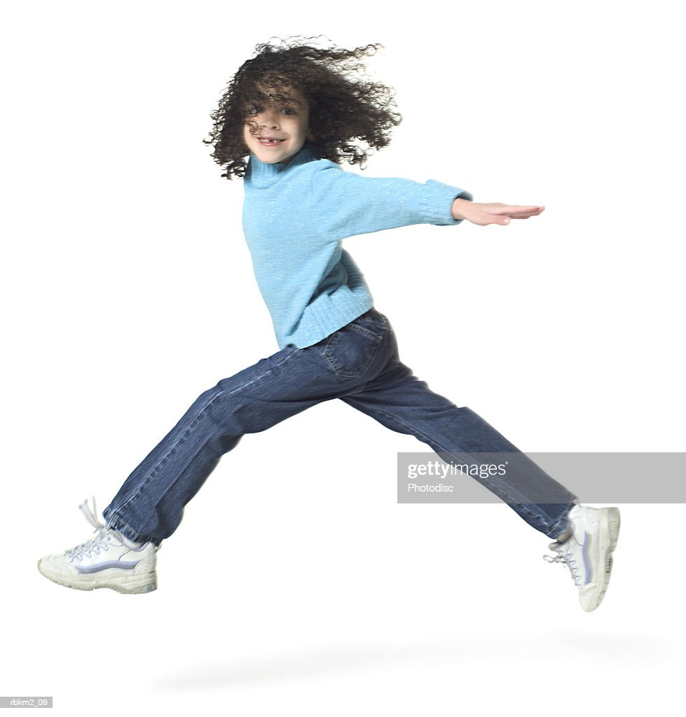 full body shot of a female child as she runs and jumps playfully through the air : Stockfoto