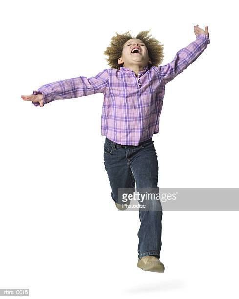 full body shot of a female child as she runs forward and throws her head back