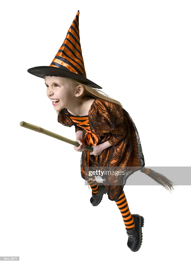 full body shot of a female child dressed as a witch for halloween as she rides a broomstick : Foto de stock