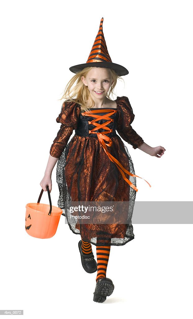 full body shot of a female child dressed as a witch for halloween as she runs with her candy pail : Foto de stock