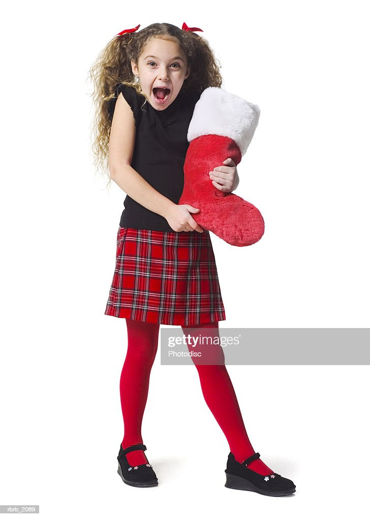 full body shot of a female child in a as she holds out a red christmas stocking : Stockfoto