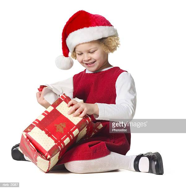 full body shot of a female child in a red dress and santa hat as she unwraps a present