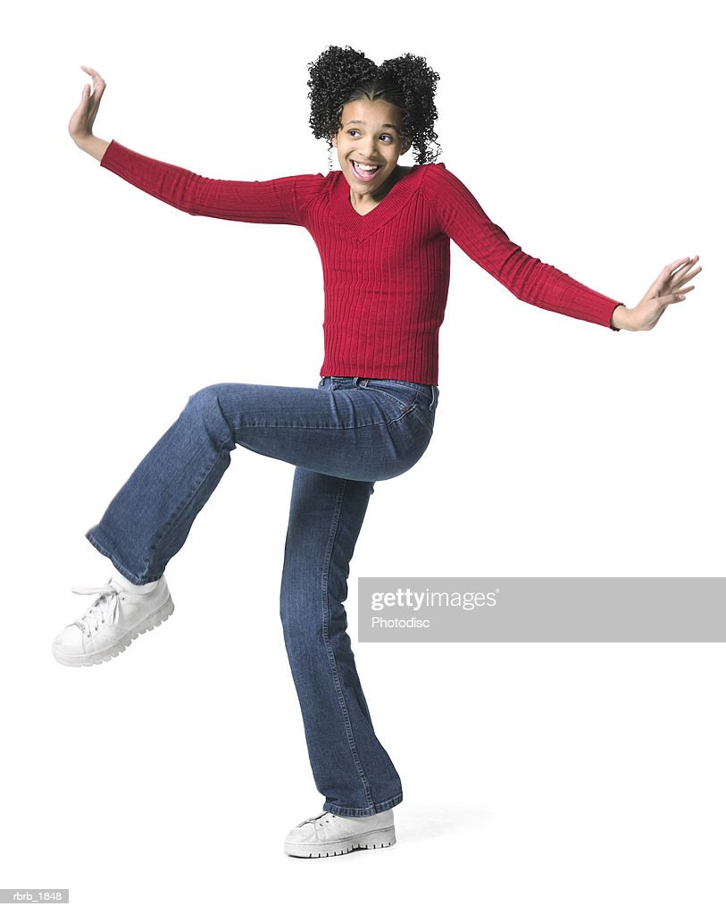 full body shot of a female child in a red sweater as she dances playfully : Stockfoto