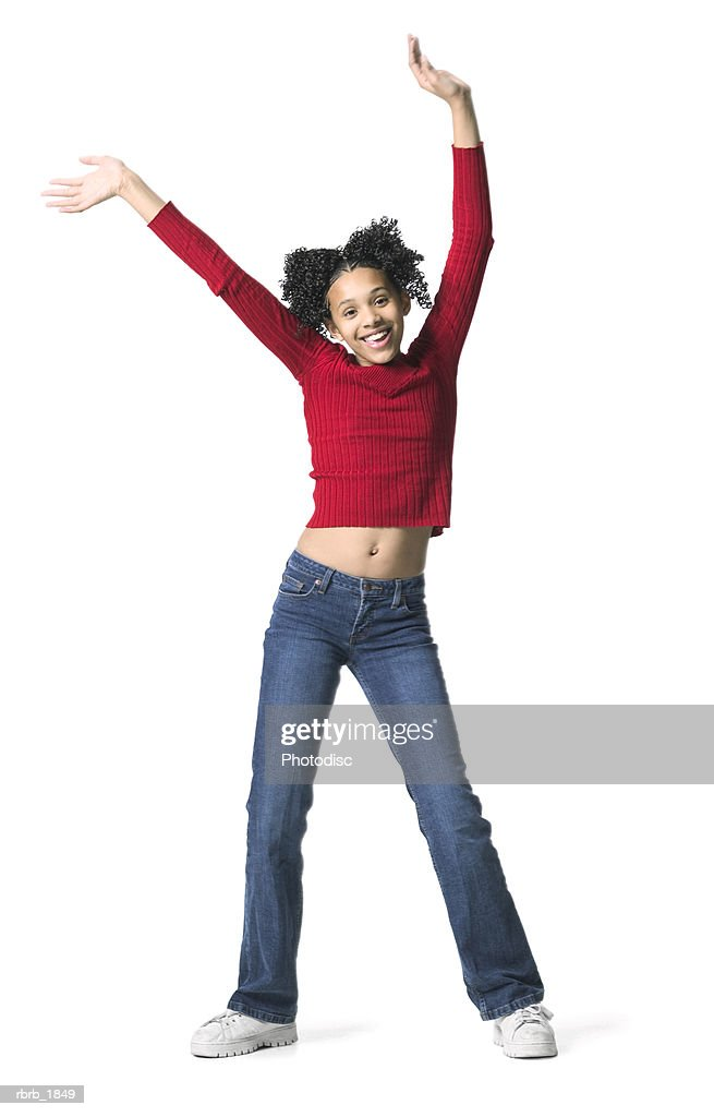 full body shot of a female child in a red sweater as she throws up her arms playfully : Stockfoto