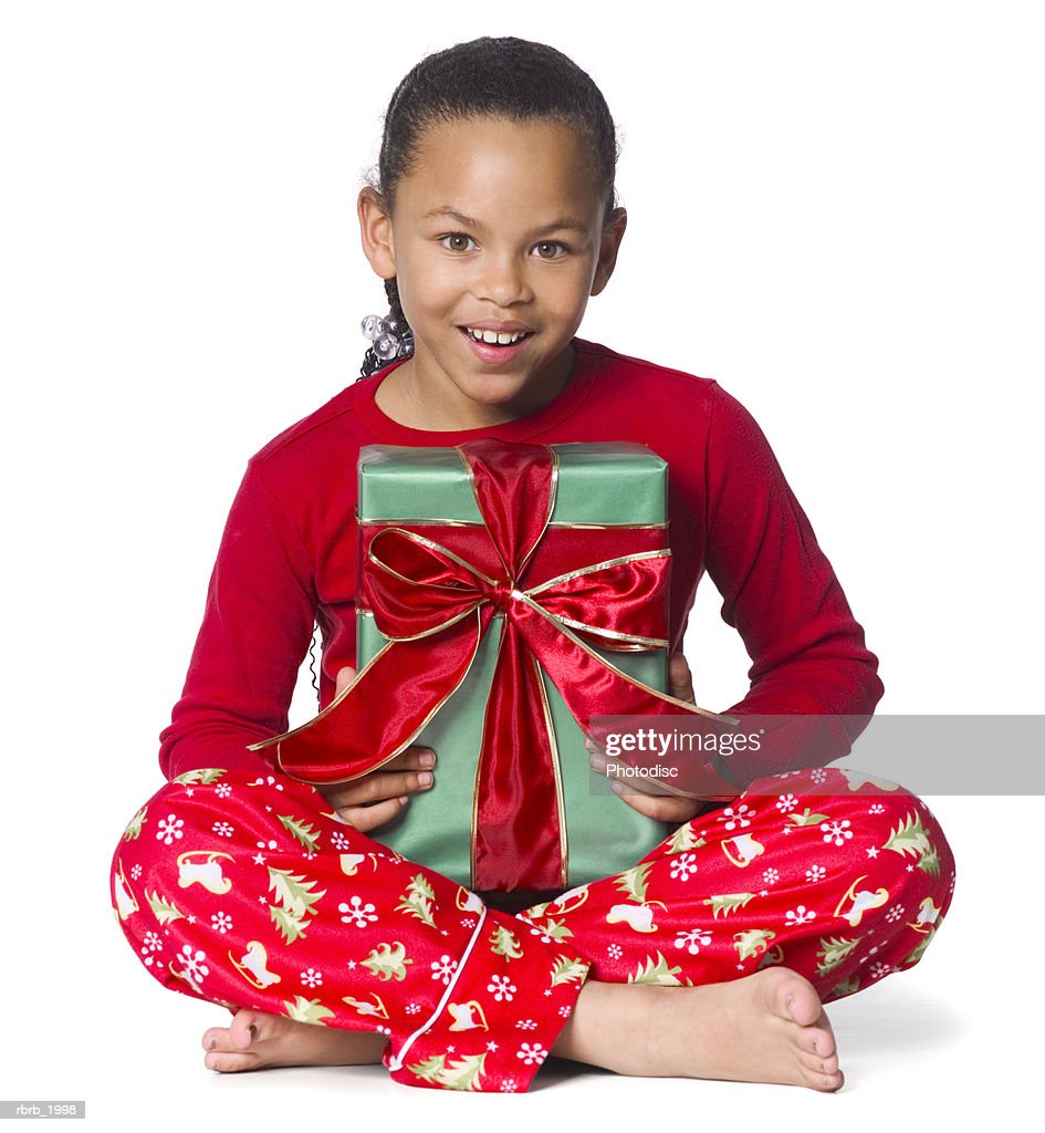 full body shot of a female child in christmas pajamas as she holds a wrapped gift on her lap : Stockfoto