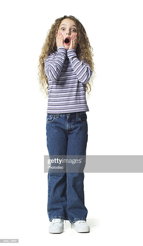 full body shot of a female child in striped shirt she puts her hands to her face and acts surprised : Stock Photo