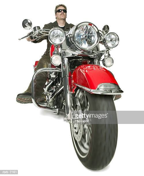 full body shot of a male biker in sunglasses and a leather jacket as he rides his red motorcycle