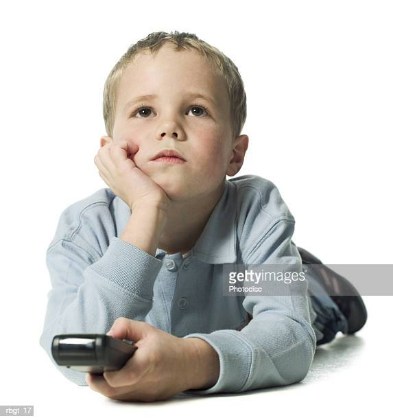 full body shot of a male child as he lays down and holds a television remote control - ligga på mage bildbanksfoton och bilder