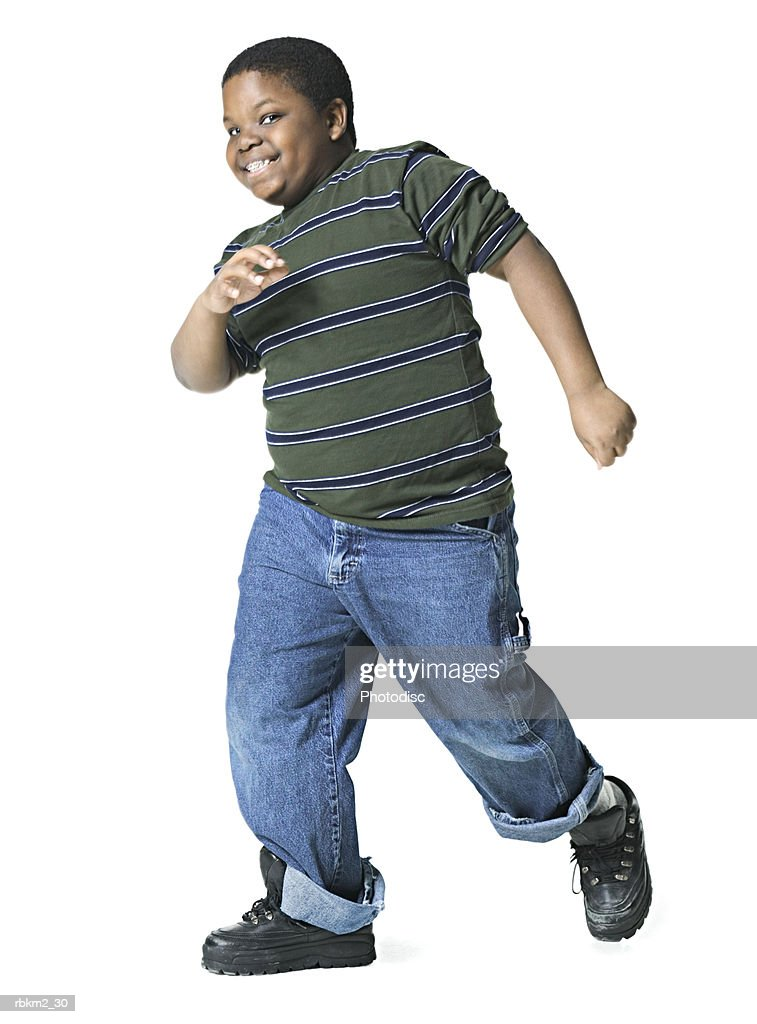 full body shot of a male child as he playfully runs to the side : Stockfoto