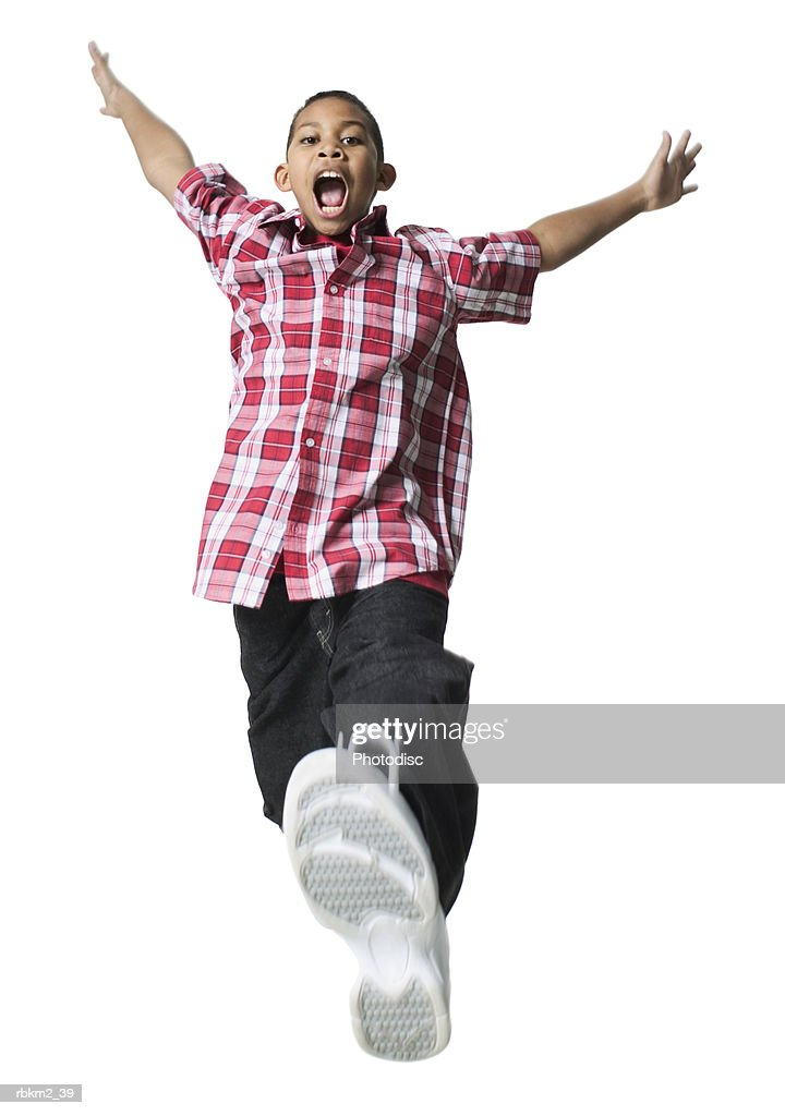 full body shot of a male child as he runs and jumps through the air : Stockfoto