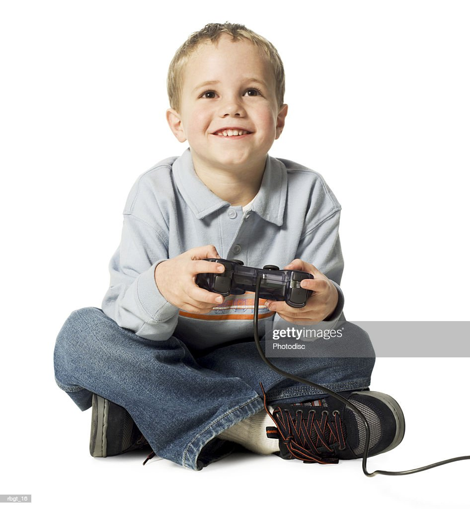 full body shot of a male child as he sits and uses a video game controler : Stockfoto