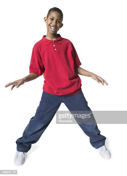 full body shot of a male child as he spreads out his arms and dances - 10 11 jaar stockfoto's en -beelden