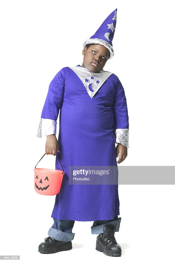 full body shot of a slightly annoyed male child dressed as a wizard for halloween : Stockfoto