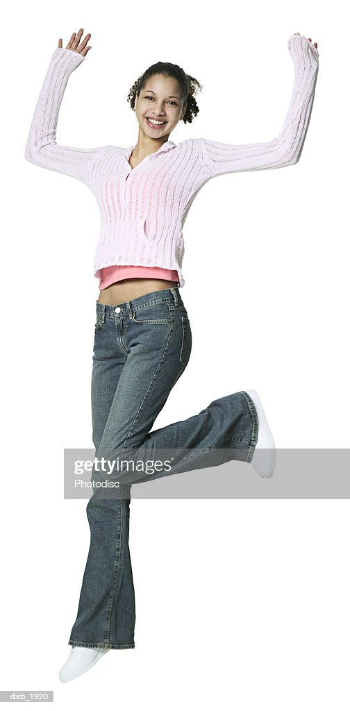 full body shot of a teenage female in a pink sweater as she jumps up through the air : Stockfoto