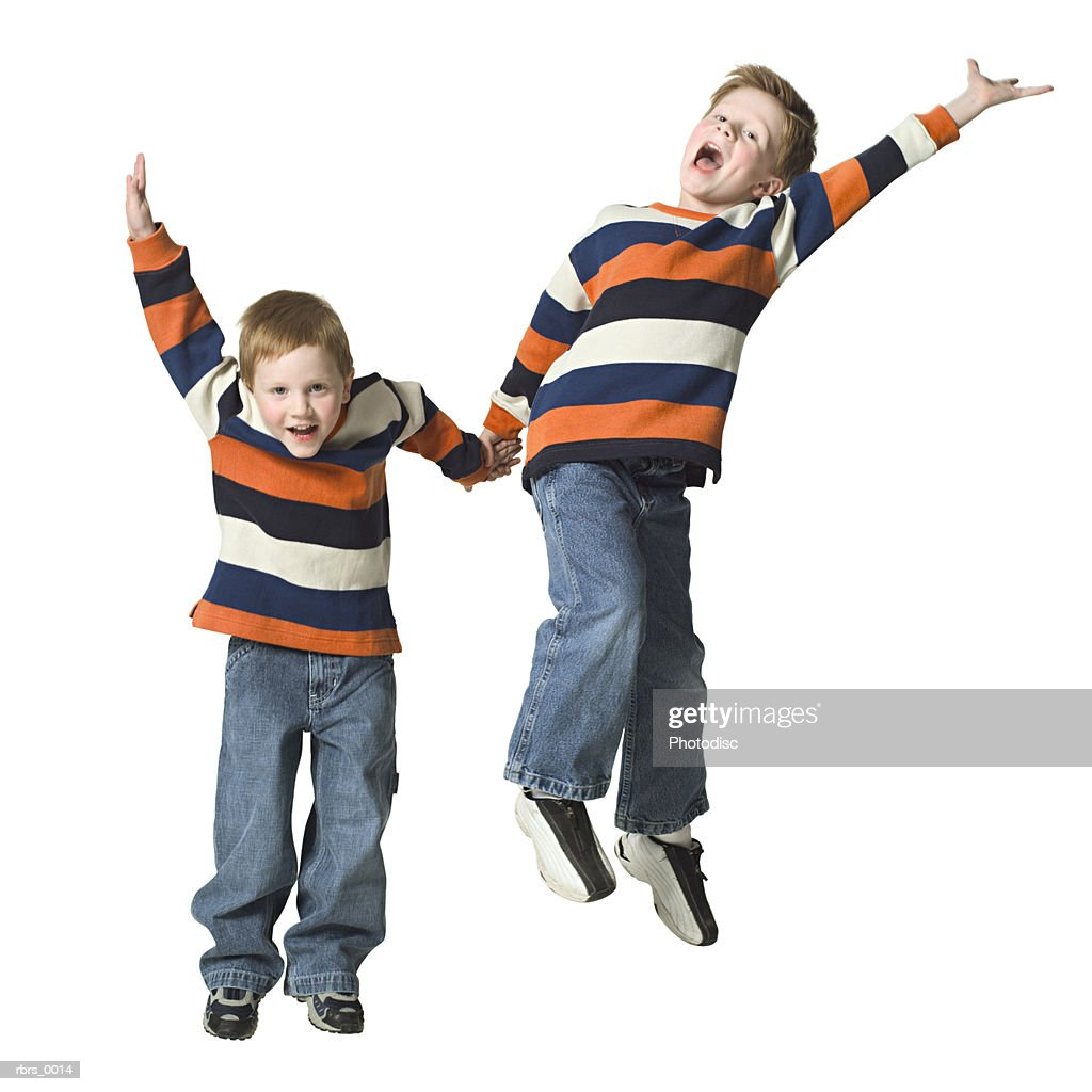 full body shot of a two male child brothers as they jumps up in the air : Foto de stock