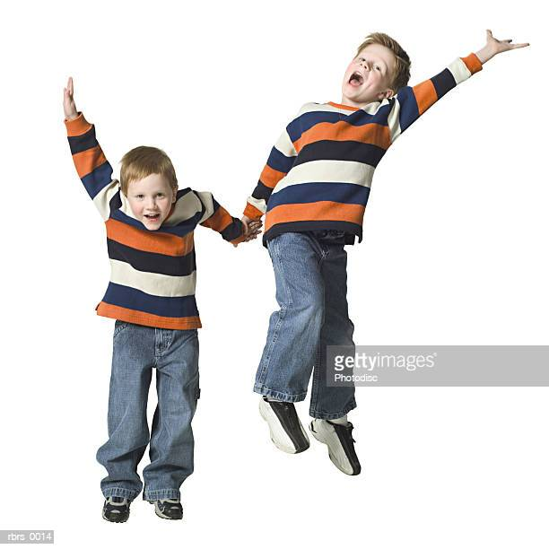 full body shot of a two male child brothers as they jumps up in the air