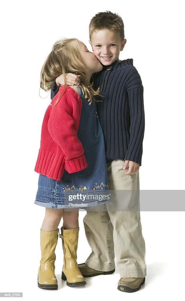 full body shot of a two sibling children as the girl kisses the boy on the cheek : Stockfoto