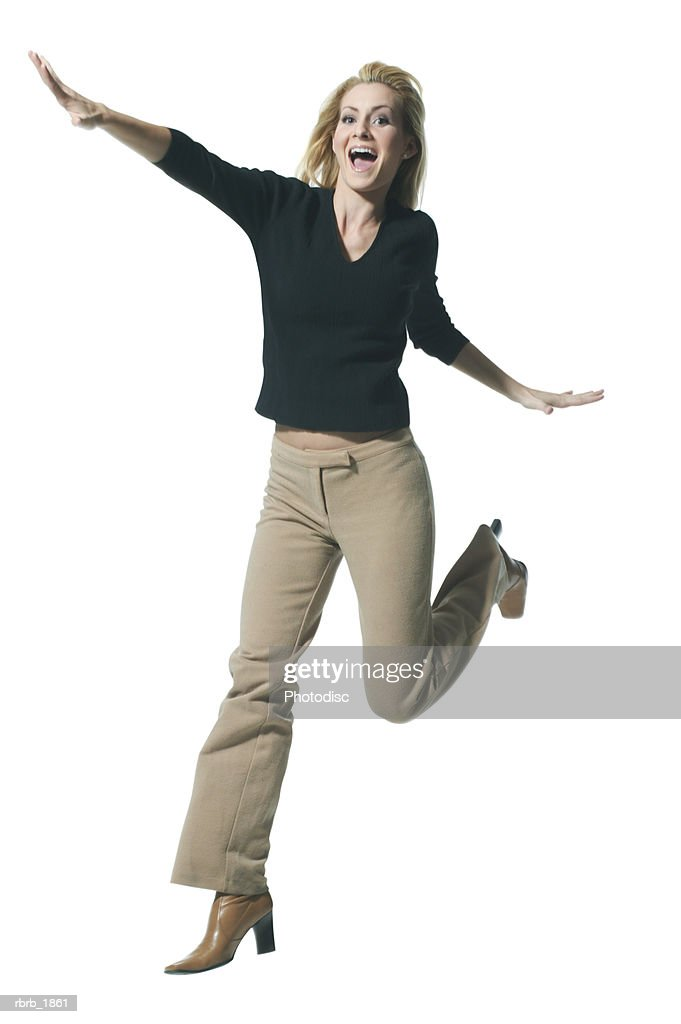 full body shot of a young adult blonde female in a black sweater as she playfully jumps through the air : Stockfoto