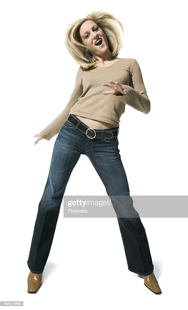 full body shot of a young adult blonde female in a tan sweater as she playfully dances : Stockfoto