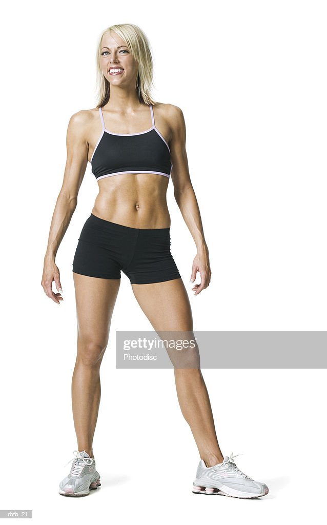 full body shot of a young adult blonde woman in a black workout outfit as she smiles : Stockfoto