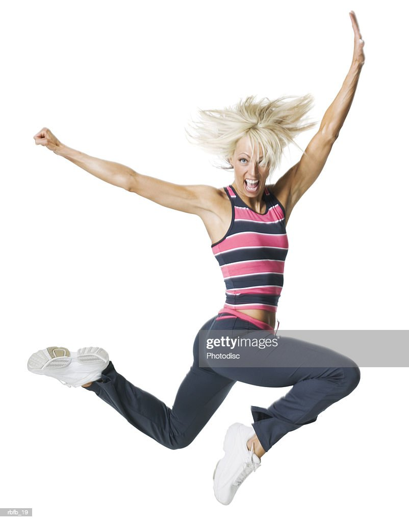 full body shot of a young adult blonde woman in a workout outfit as she jumps through the air : Stockfoto