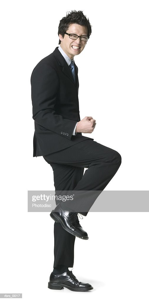 full body shot of a young adult business man as he celebrates a job well done : Foto de stock