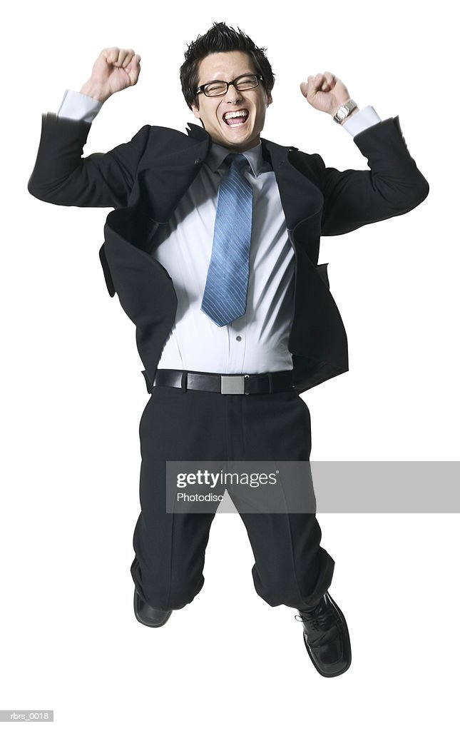 full body shot of a young adult business man as he jumps up in celebration : Foto de stock