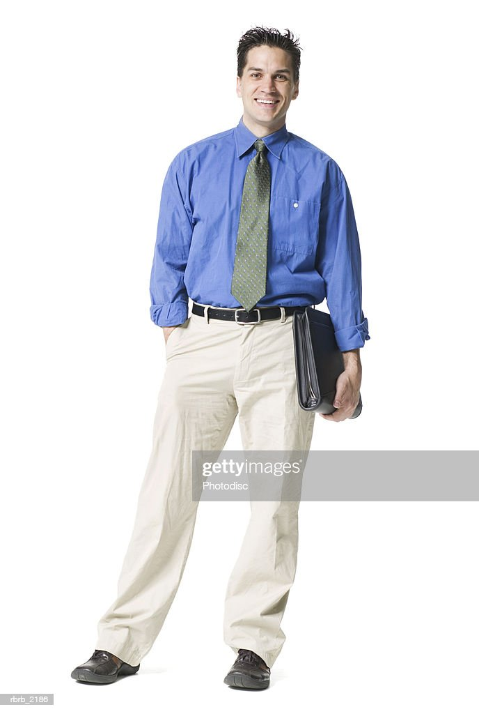 full body shot of a young adult business man in a blue shirt and tie he holds a notebook and smiles : Foto de stock