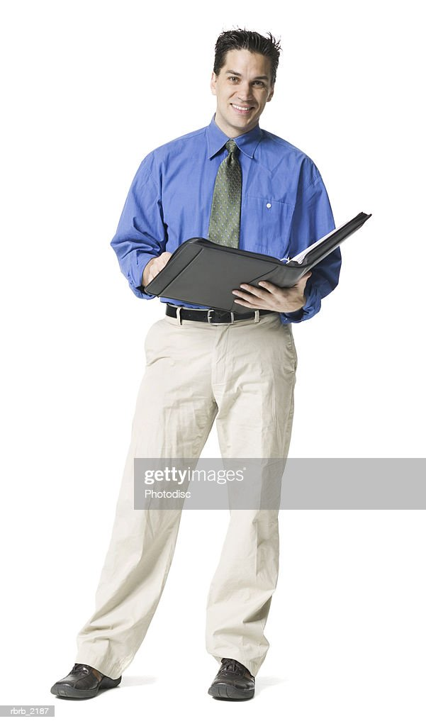 full body shot of a young adult business man in a blue shirt and tie as he looks into a notebook and smiles : Foto de stock