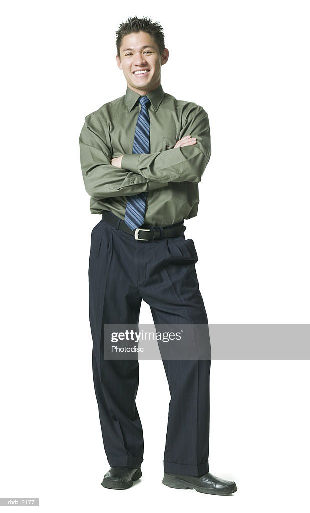 full body shot of a young adult business man in a green shirt as he folds his arms and smiles : Stockfoto