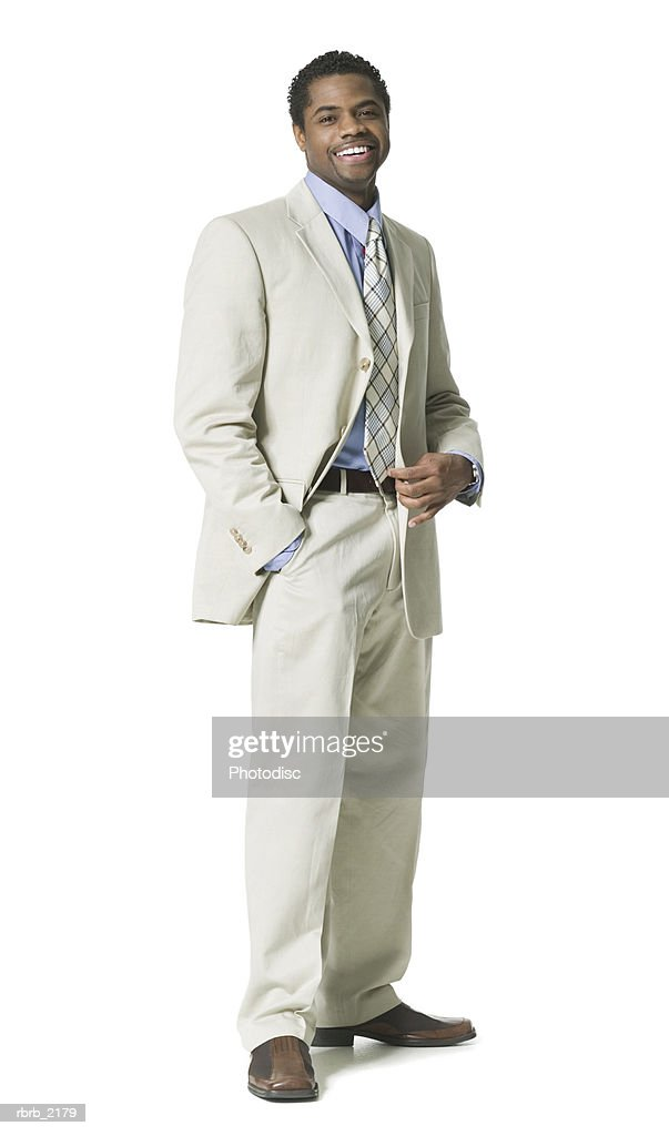 full body shot of a young adult business man in a light suit as he smiles : Foto de stock