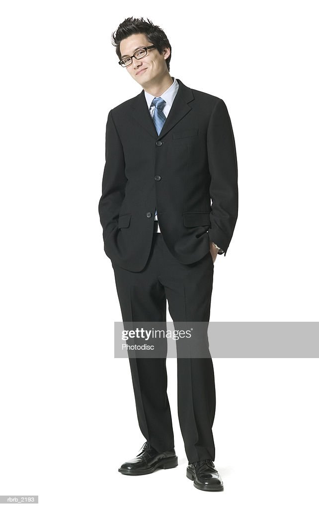 full body shot of a young adult business man in a suit as he puts his hand on his pockets and smirks : Foto de stock