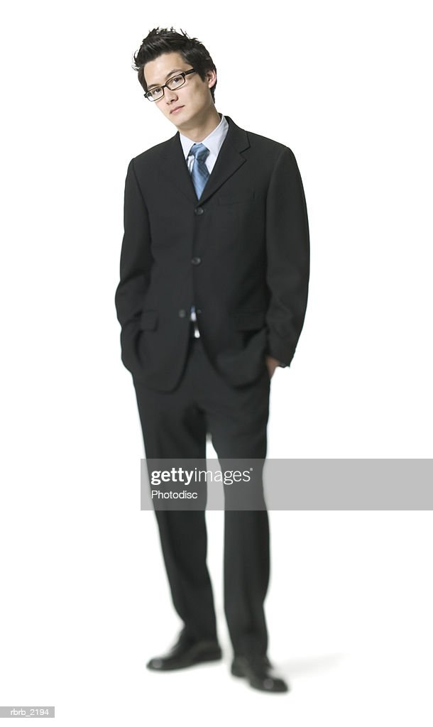 full body shot of a young adult business man in a suit as he puts his hand on his pockets : Foto stock