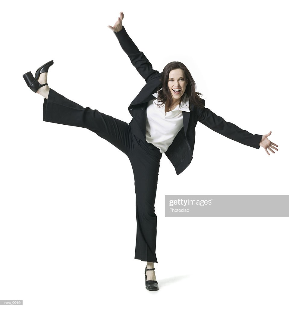 full body shot of a young adult business woman as she kicks up into the air : Foto de stock