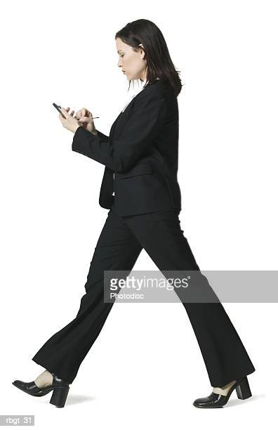 full body shot of a young adult business woman as she walks using her palm pilot