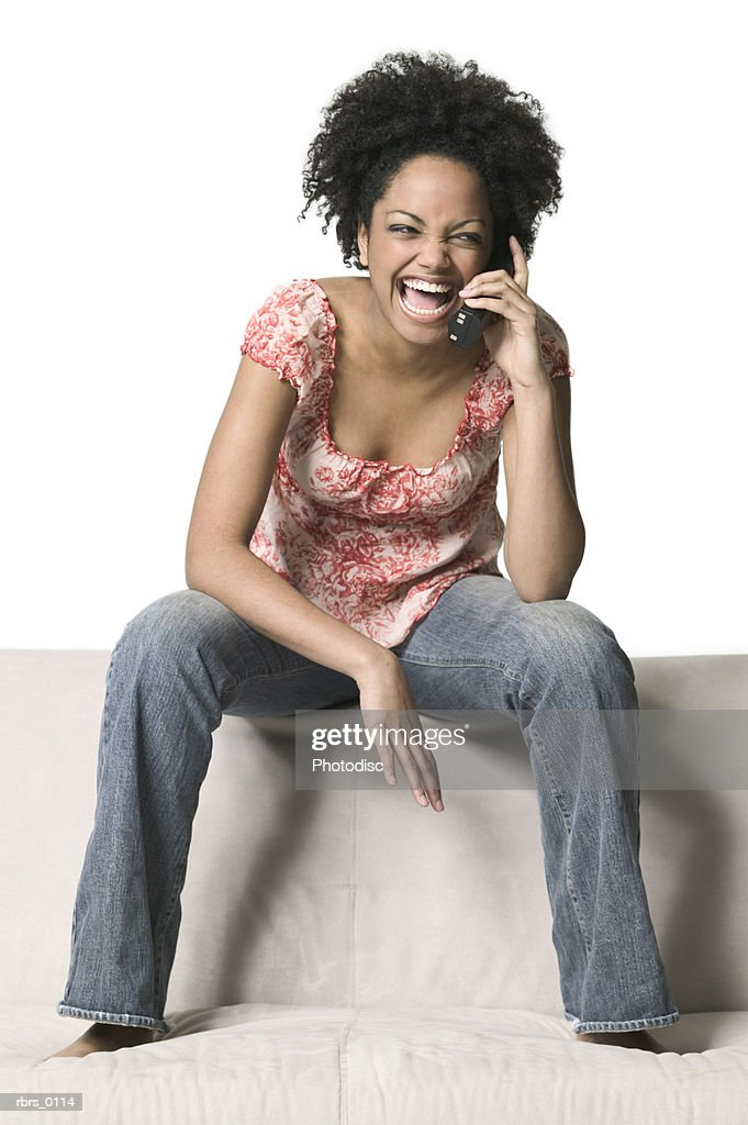 full body shot of a young adult female as she sits on top of a couch and chats on a cell phone : Foto de stock