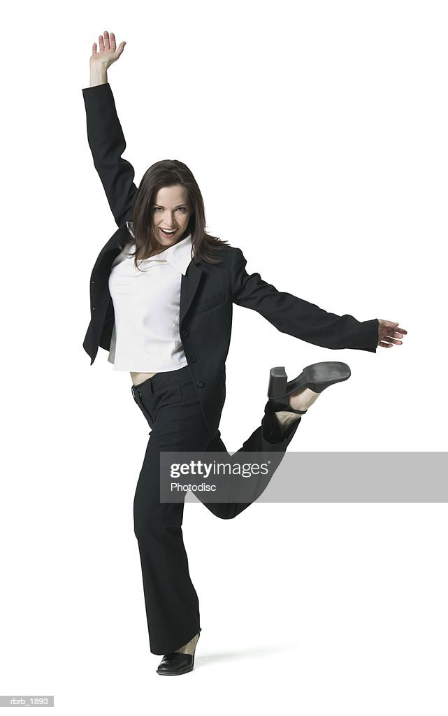 full body shot of a young adult female in a black pant suit as she playfully skips and dances around : Stockfoto