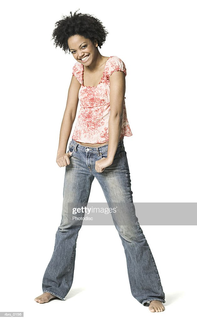 full body shot of a young adult female in a floral shirt as she shrugs and smiles : Foto de stock