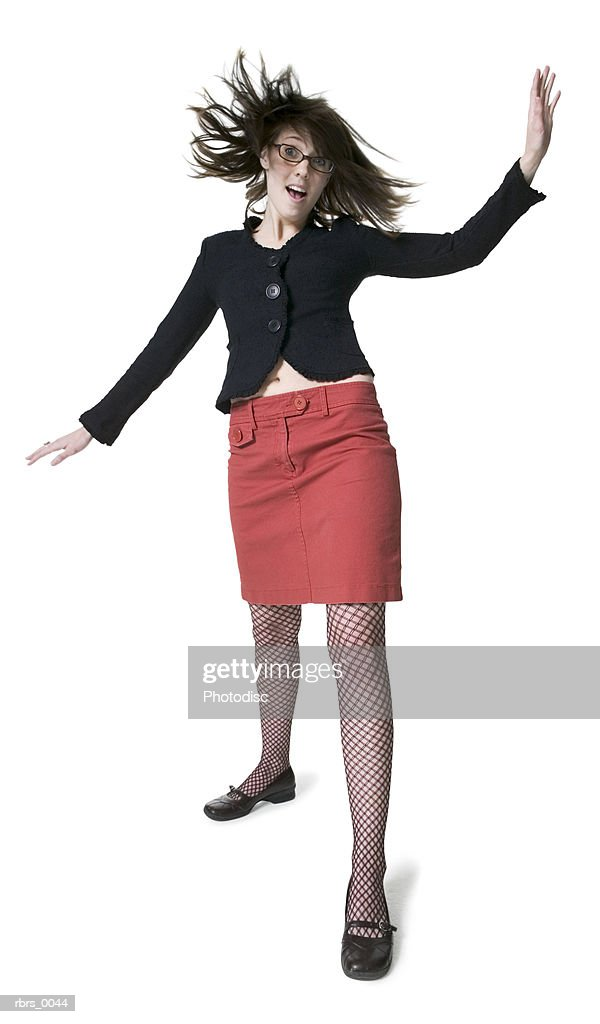 full body shot of a young adult female in a red skirt as she moves around playfully : Foto de stock