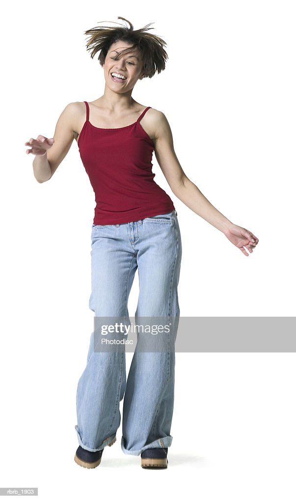 full body shot of a young adult female in a red tank top as she playfully dances : Stockfoto