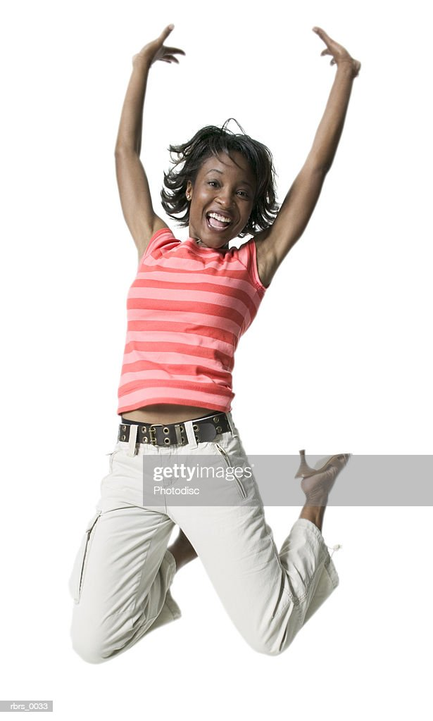 full body shot of a young adult female in a striped shirt as she jumps into the air : Foto de stock