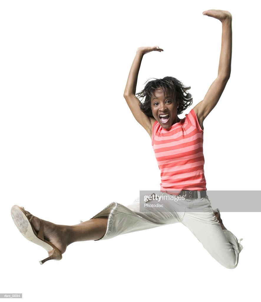 full body shot of a young adult female in a striped shirt as she runs and jumps through the air : Foto de stock