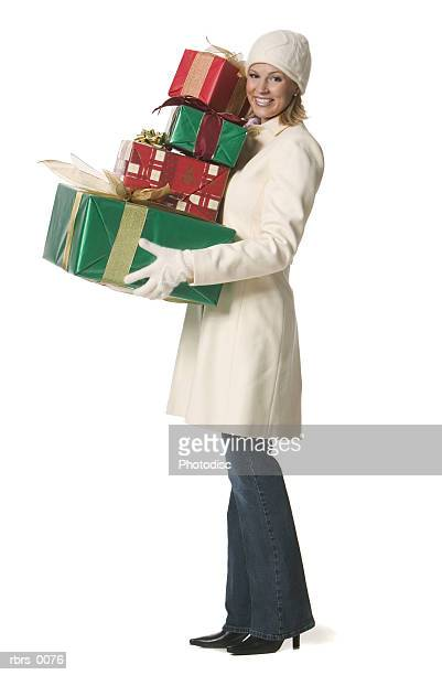 full body shot of a young adult female in a winter coat as she hold up a pile of christmas gifts