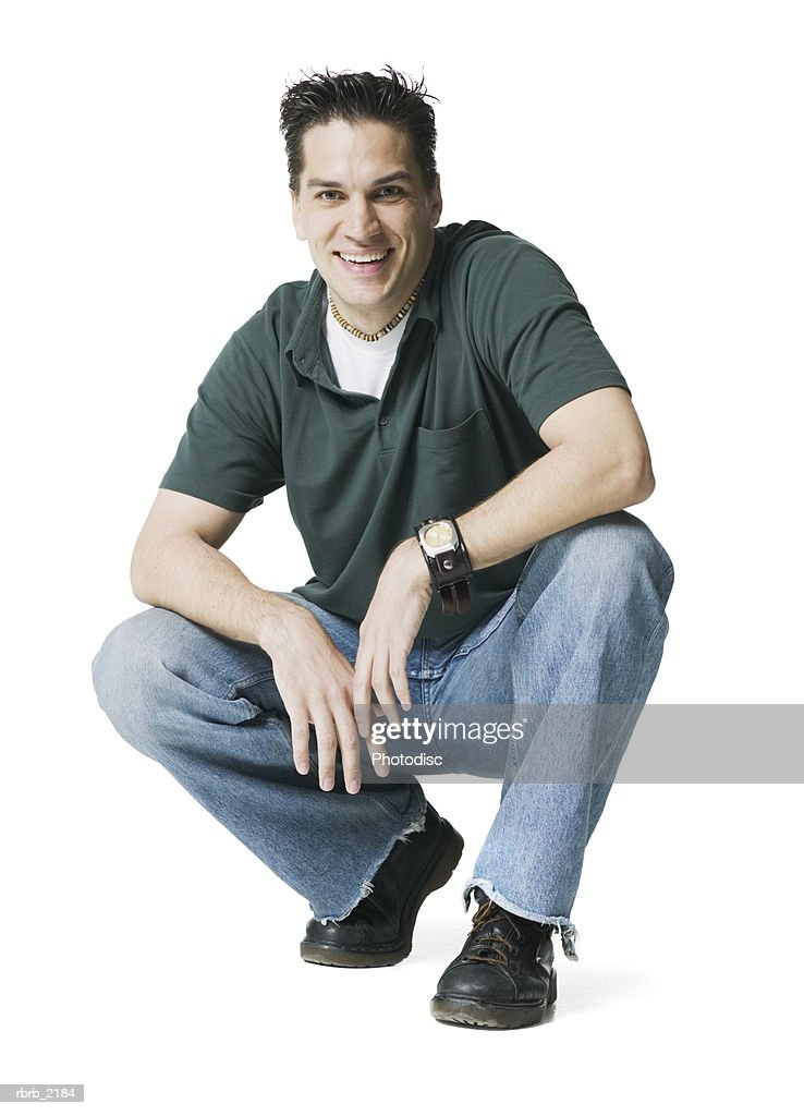 full body shot of a young adult male as he crouches down and smiles at the camera : Foto de stock