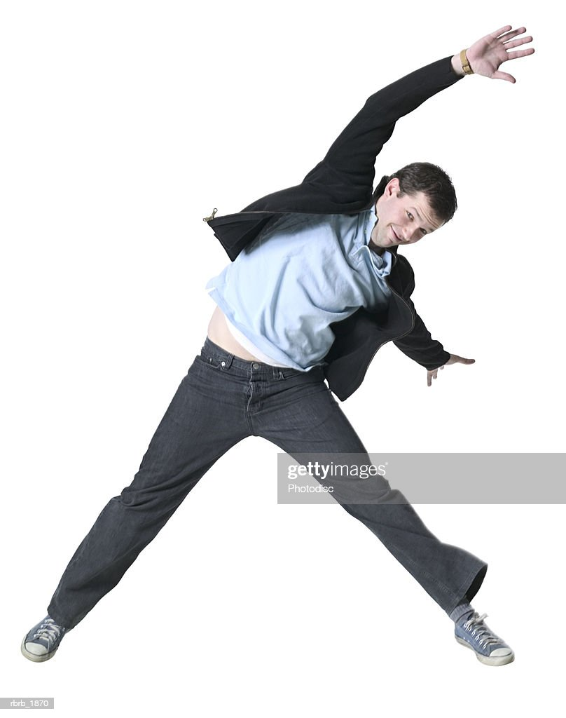 full body shot of a young adult male in a black jacket as he jumps through the air : Stockfoto