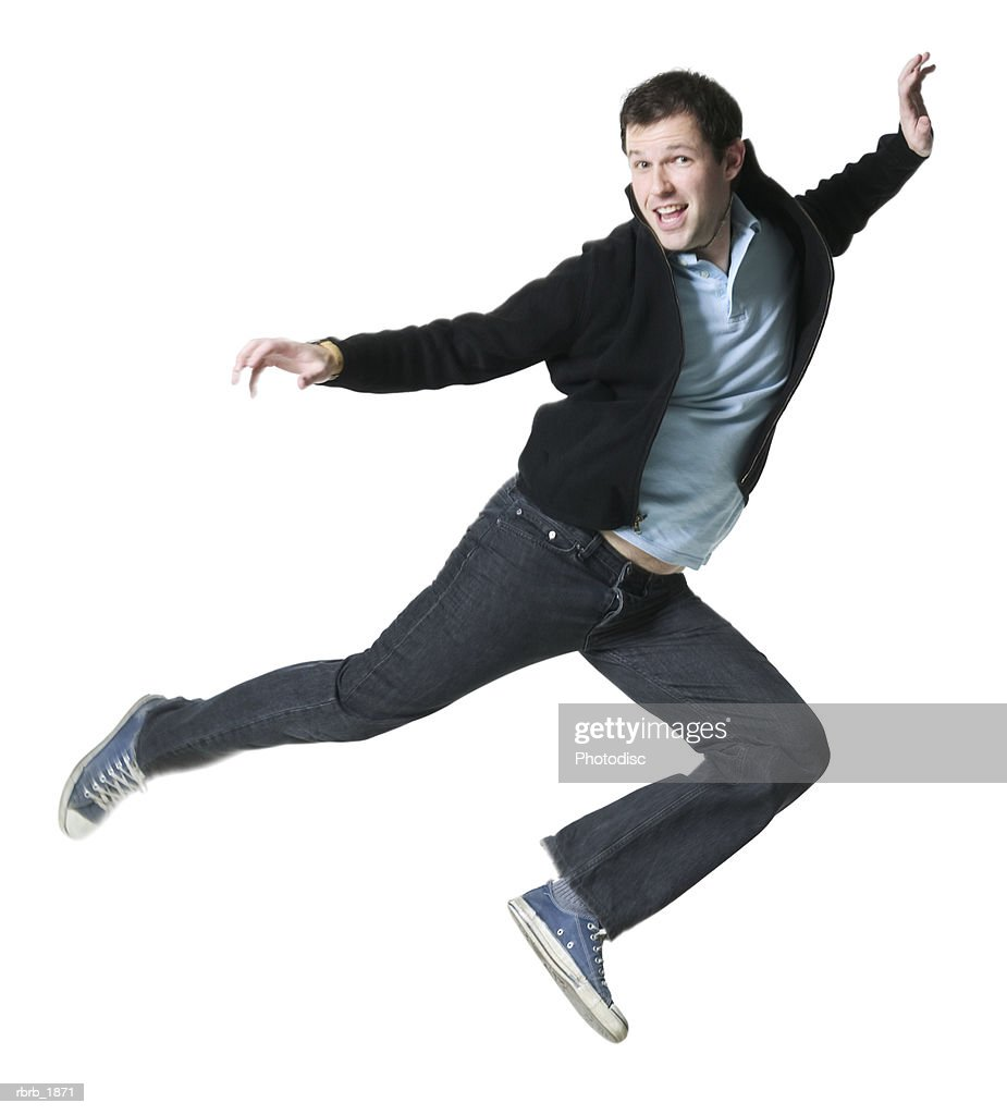 full body shot of a young adult male in a black jacket as he playfully jumps through the air : Stockfoto